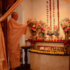 Guru Maharaja offering arati to the Deities